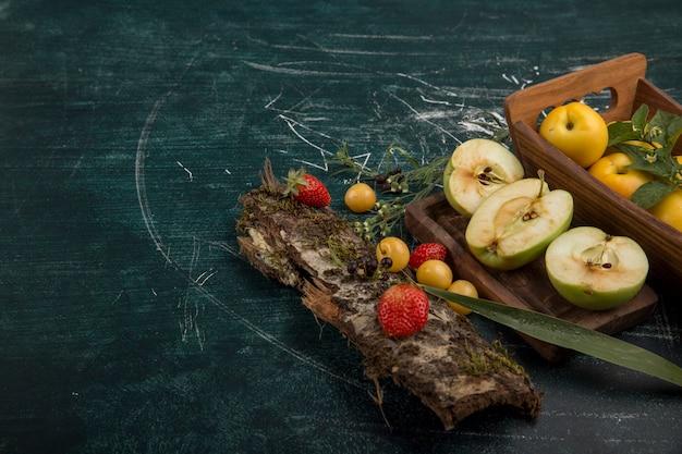 Prato redondo de frutas com peras, maçã e frutas vermelhas em fundo fosco