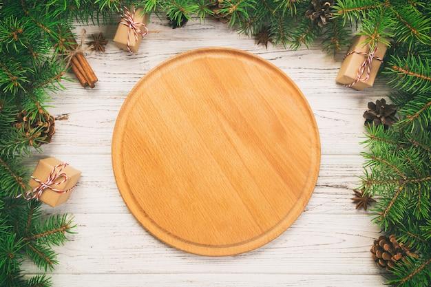 Prato redondo de madeira vazio com galhos de árvores de abeto e paus de canela