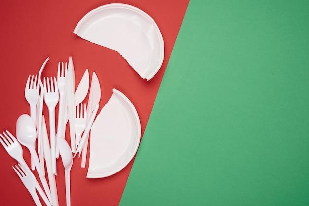 Prato redondo e pilha de garfos e colheres de plástico