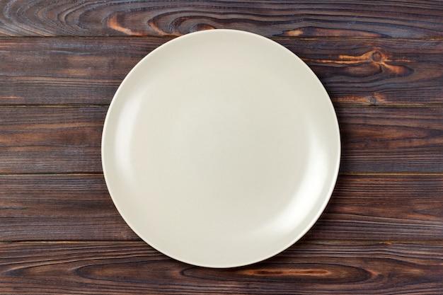 Prato redondo fosco vazio na mesa de madeira. vista do topo