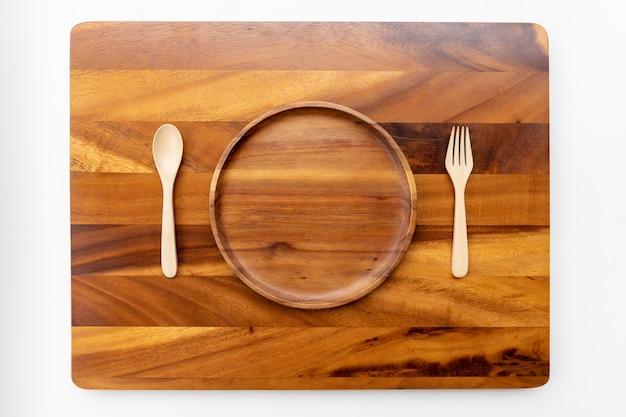 Prato redondo, madeira lacada, lacado com uma colher e um garfo, apoiado em uma placa de madeira feita de acácia, com espaço para texto