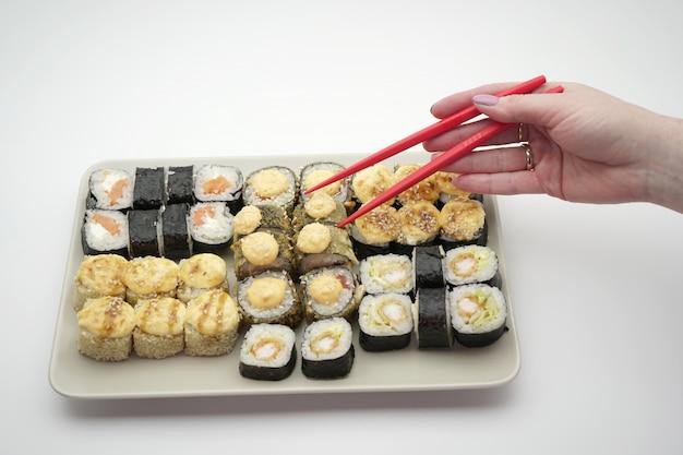 Prato retangular cheio de sushi rolls e palitos de cor vermelha, sobre um fundo isolado, close-up
