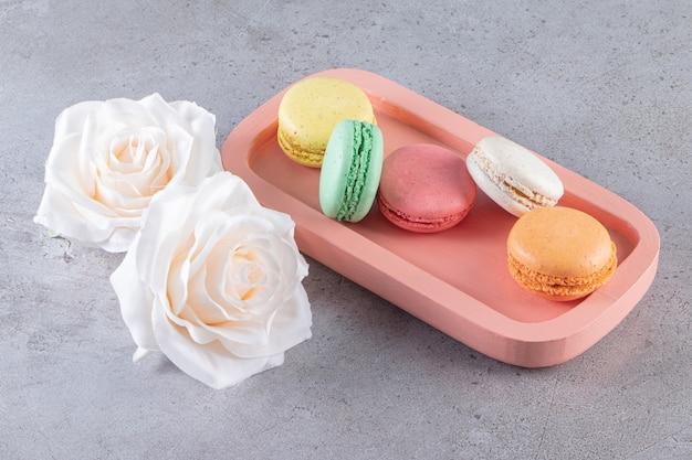 Prato rosa de bolos de amêndoa doce com rosas brancas na mesa de pedra.