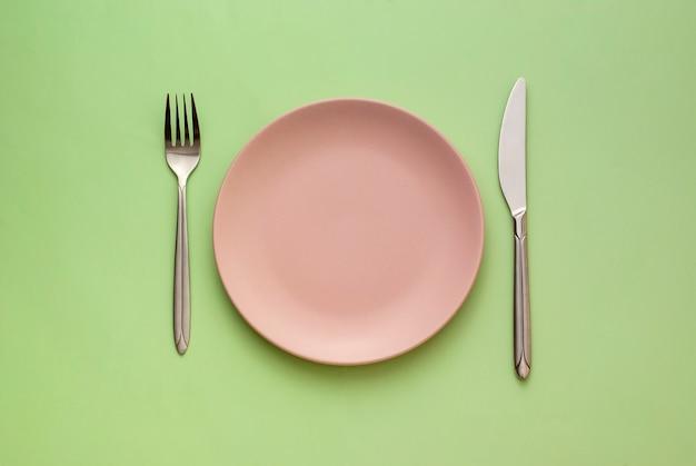 Prato rosa vazio com utensílios em verde
