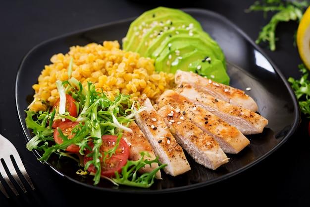 Prato saudável com frango, tomate, abacate, alface e lentilha na mesa escura