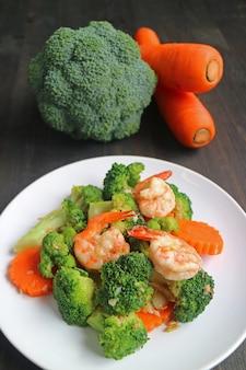 Prato saudável de camarão frito com brócolis e cenoura, servido no prato branco