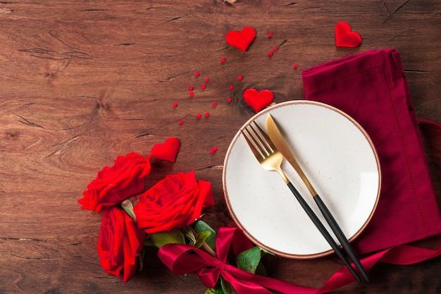 Prato, talheres e rosas vermelhas na mesa de madeira, conceito de jantar romântico