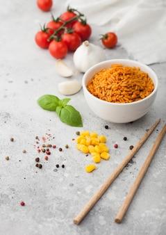 Prato tigela de cerâmica branca com arroz basmati de grão longo vermelho cozido com legumes em fundo claro com palitos e tomates com milho, alho e manjericão.