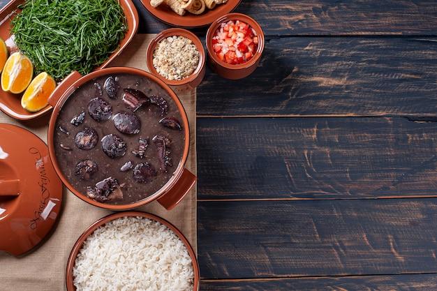 Prato típico brasileiro chamado feijoada. feito com feijão preto, porco e linguiça. vista do topo. copie o espaço