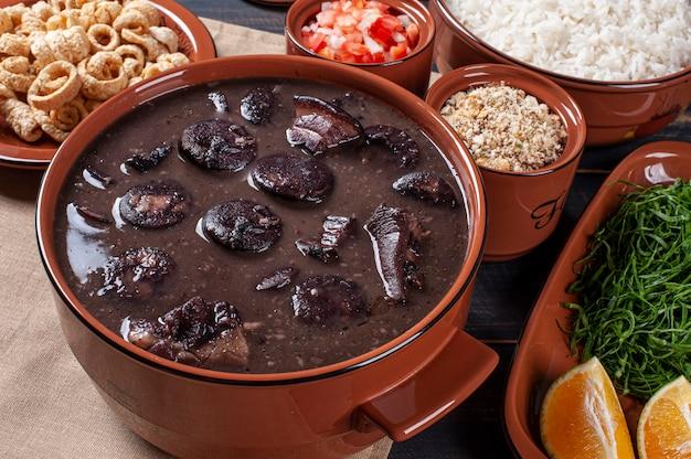 Prato típico brasileiro chamado feijoada. feito com feijão preto, porco e linguiça Foto Premium