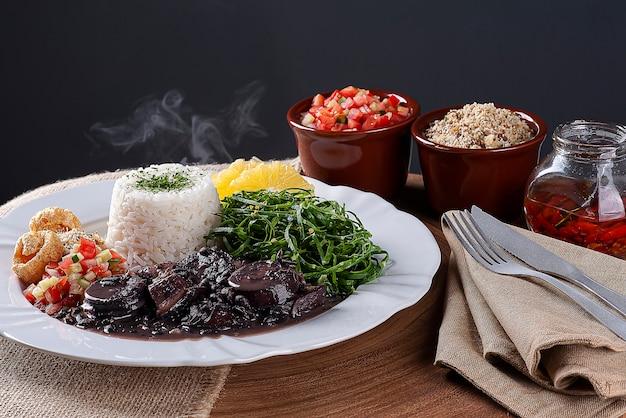 Prato típico da culinária brasileira chamado feijoada, com feijão preto, bacon, linguiça e porco