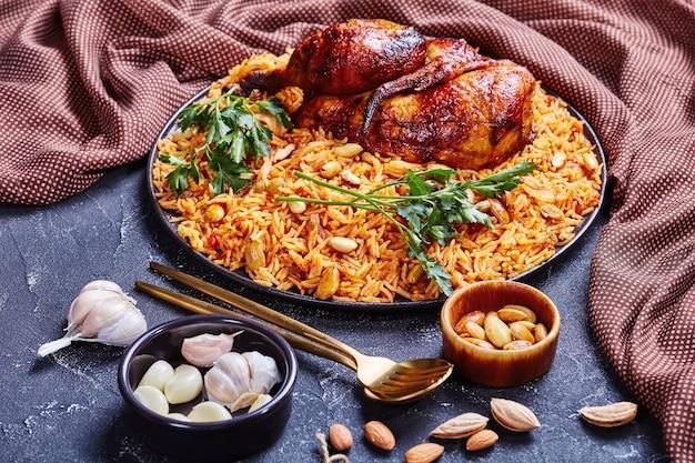 Prato tradicional da arábia saudita com frango e arroz kabsa com especiarias, amêndoas torradas, passas e alho em um prato preto