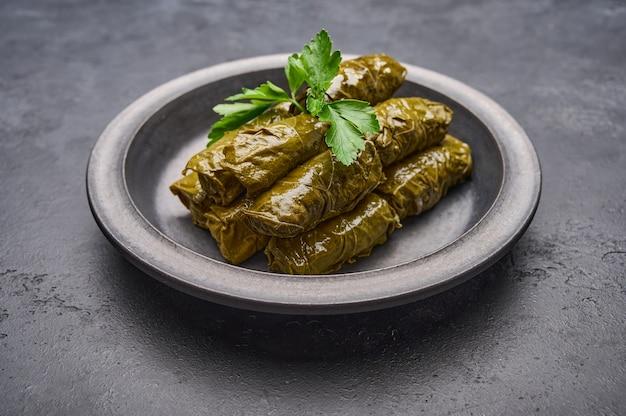 Prato tradicional do oriente médio dolma ou tolma com salsa em placa preta sobre fundo de madeira escura