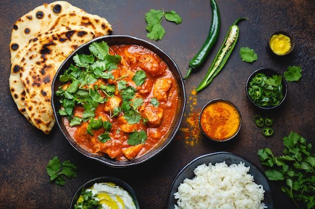 Prato tradicional indiano frango tikka masala com carne picante de curry na tigela, arroz basmati, pão naan, molho raita de iogurte em fundo escuro rústico, vista superior, close-up. jantar estilo indiano de cima