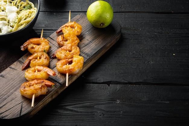 Prato tradicional italiano. conjunto de macarrão com pesto de ricota parmesão e frutos do mar grelhados, em mesa de madeira preta