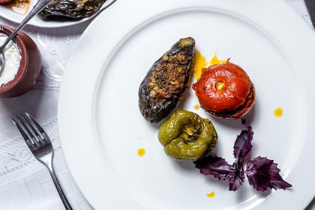 Prato tradicional três irmãs dolma pimentão tomate e berinjela preenchido por carne picada manjericão vista lateral