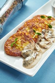 Prato tradicional ucraniano e bielorrusso - panquecas de batata frita (draniki, deruny) com creme de leite e cogumelos porcini, servido em um prato branco sobre uma mesa azul