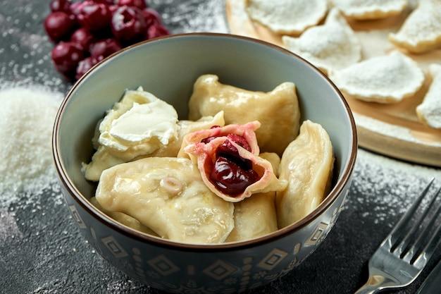Prato tradicional ucraniano ou polonês - pierogi ou varenyky (bolinhos) recheado com cereja e creme de leite em uma mesa escura. close up, foco seletivo