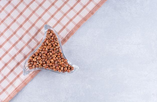 Prato trinagular ornamentado cheio de feijões vermelhos na toalha de mesa, na superfície de mármore