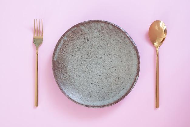 Prato vazio, ajuste de tabela. prato de cerâmica, colher e um garfo no fundo rosa cor pastel
