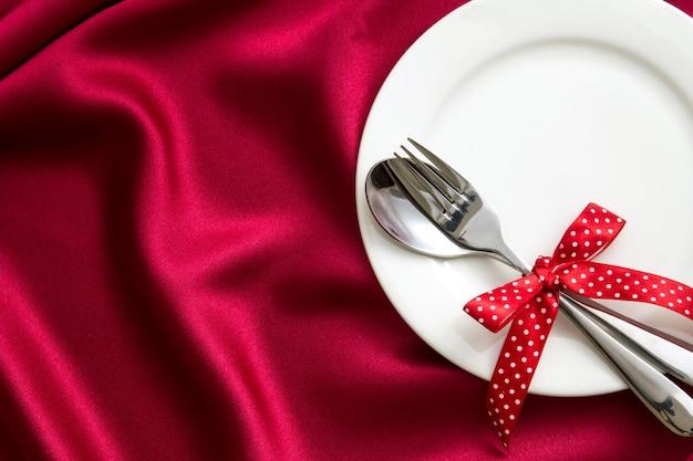 Prato vazio branco com garfo e colher em tecido de seda vermelho para configuração de jantar