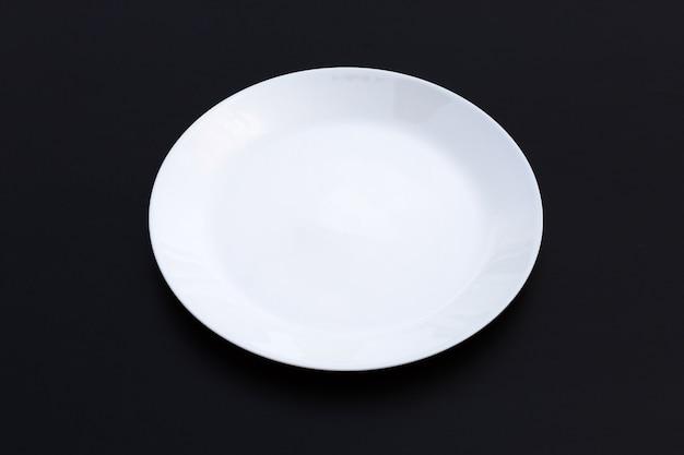 Prato vazio branco na superfície escura. copie o espaço