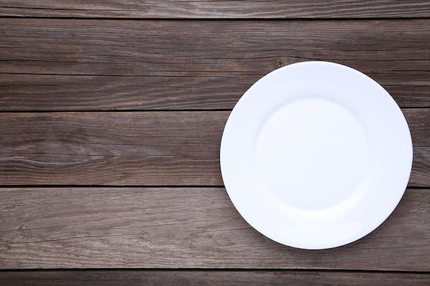 Prato vazio branco sobre um fundo cinza de madeira