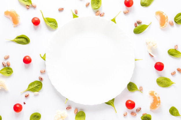 Prato vazio cercado por feijão pinto; legumes e fatias de laranja, dispostas em fundo branco