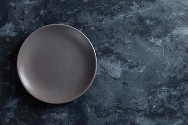 Prato vazio cinzento sobre um fundo escuro e concreto, um espaço em branco para o projeto. copie o espaço.