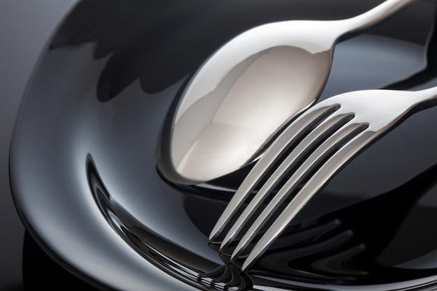 Prato vazio com colher e garfo em um preto