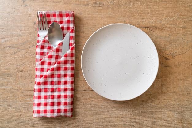 Prato vazio com faca, garfo e colher na superfície do ladrilho de madeira