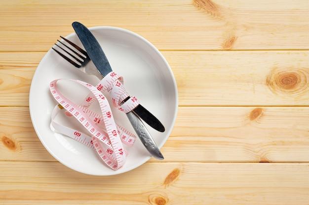 Prato vazio com fita métrica, faca e garfo