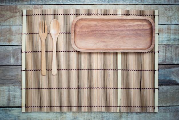 Prato vazio com garfo e colher na mesa de madeira