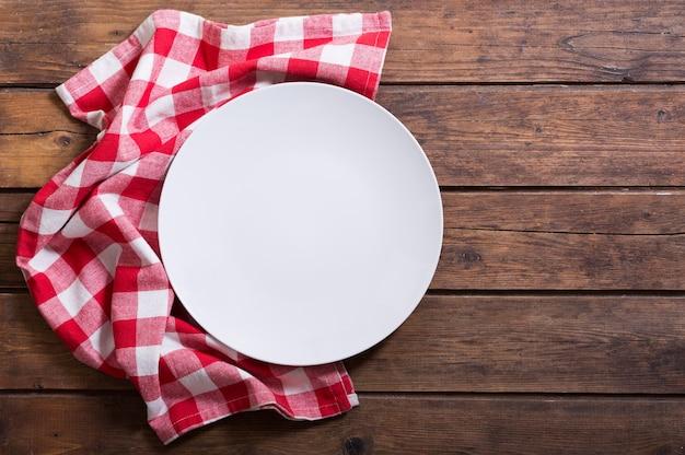 Prato vazio com toalha de mesa vermelha na mesa de madeira, vista superior