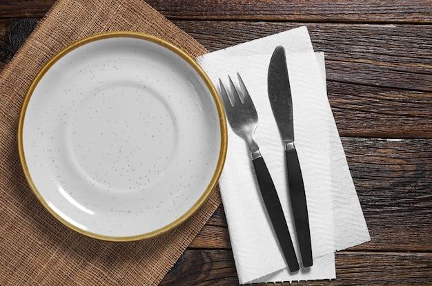 Prato vazio com velho garfo e faca na velha mesa de madeira. vista do topo