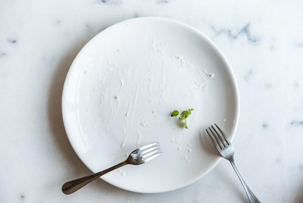 Prato vazio de bolo com garfo na mesa