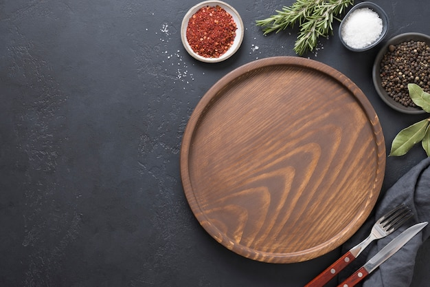 Prato vazio de madeira, temperos e ingredientes para cozinhar. vista de cima.