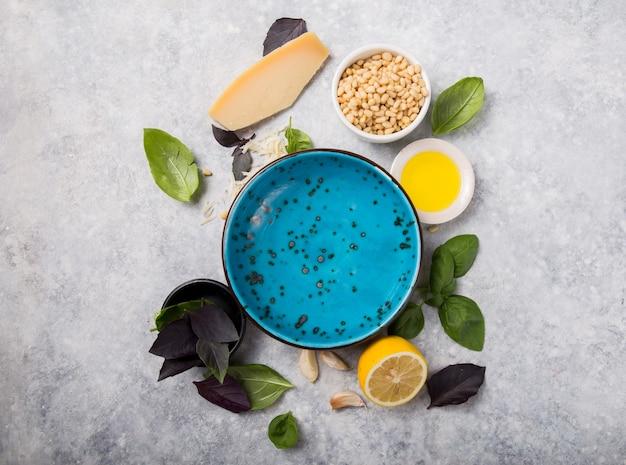 Prato vazio de molho pesto de manjericão italiano com ingredientes culinários para cozinhar