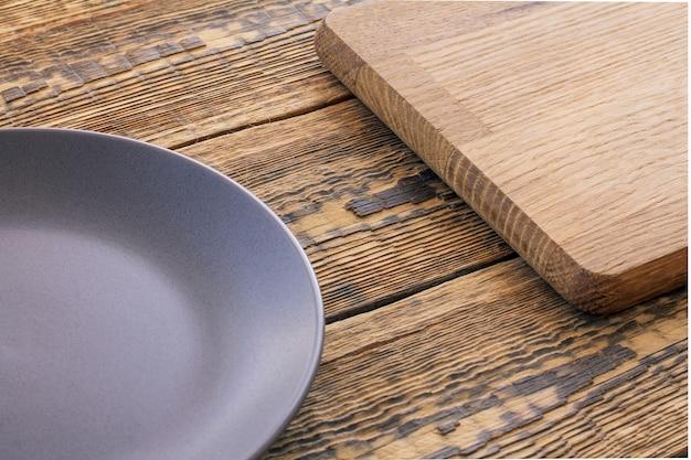 Prato vazio de porcelana cinza e tábua de cortar madeira em tábuas de madeira marrons