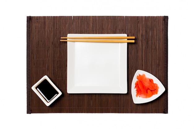 Prato vazio do quadrado branco com pauzinhos para molho de sushi, gengibre e soja na esteira de bambu escuro.