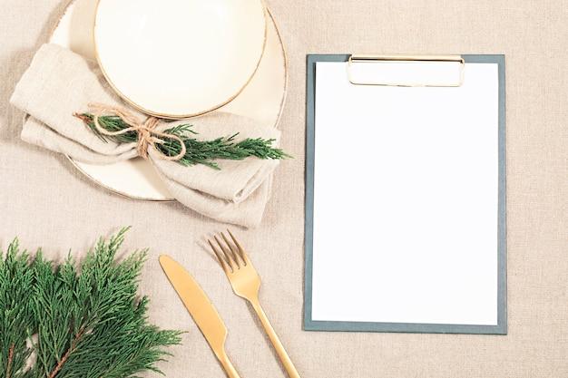 Prato vazio e galhos de árvore do abeto na toalha de mesa de linho em cores neutras naturais. camada plana, vista superior