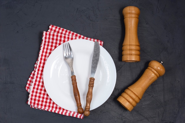Prato vazio e guardanapo na mesa preta