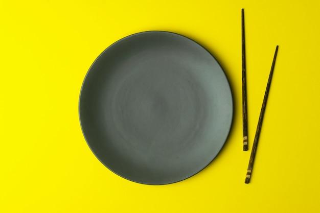 Prato vazio em um fundo amarelo. prato vazio para comida asiática e chinesa e cozinha com pauzinhos chineses
