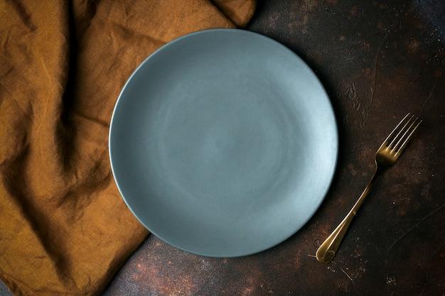 Prato vazio em um fundo escuro. esvazie o prato de cerâmico cinzento com uma faca e um garfo para comida e jantar em um fundo bonito e escuro.