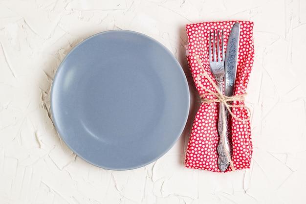 Prato vazio, faca, garfo e guardanapo sobre fundo branco de mesa. vista de cima com espaço de cópia.