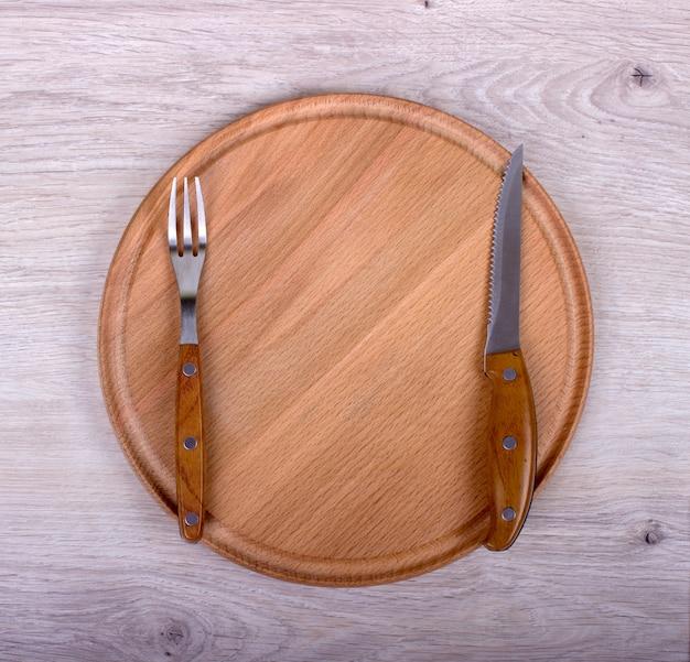 Prato vazio, garfo e faca em fundo de madeira.