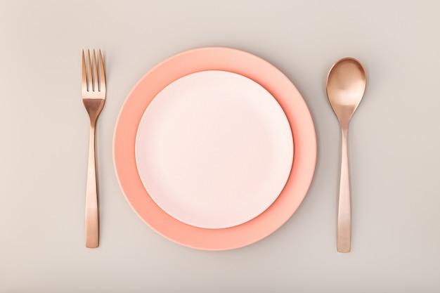 Prato vazio, garfo e faca na mesa. tons pastel rosa. brincar