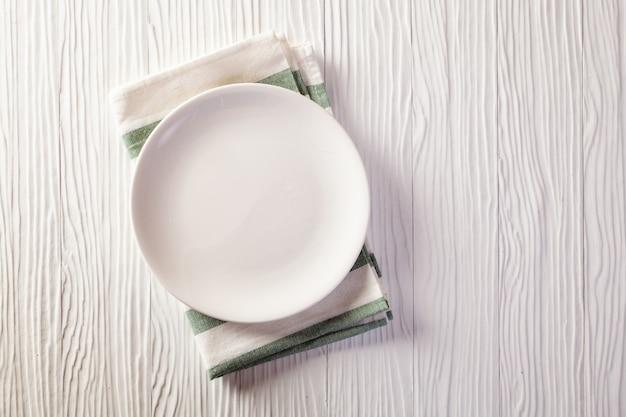 Prato vazio na toalha de mesa quadriculada na mesa de madeira branca