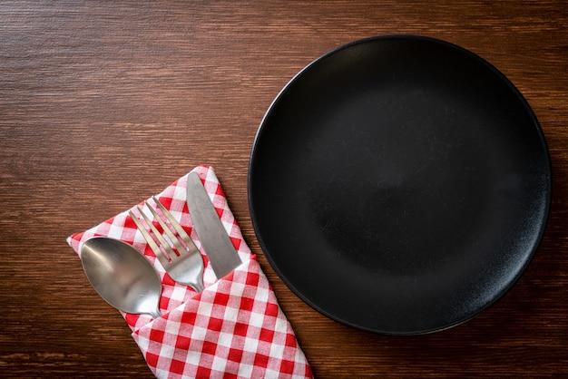 Prato vazio ou prato com faca, garfo e colher na mesa de madeira