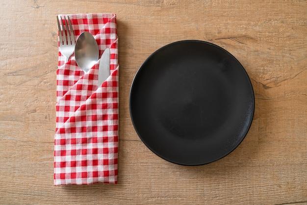 Prato vazio ou prato com faca, garfo e colher na superfície do ladrilho de madeira